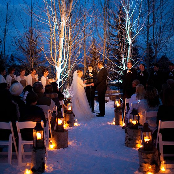 candle lanterns standing on tree stumps for warming up a winter wedidng aisle