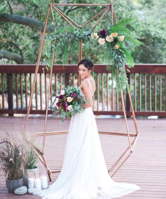 copper dimensional wedding arbor with greenery and flowers for a modern feel