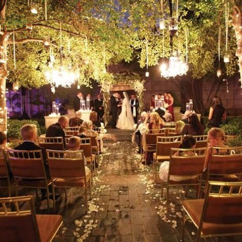 crystal chandeliers and candle holders hanging over the whole ceremony space