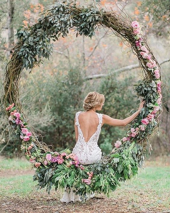 oversized grapevine wreath with greenery and pink roses can be used as a swing for the bride