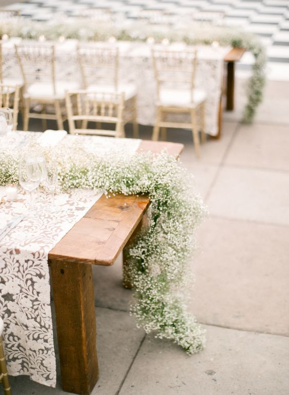 long baby's breath garlands on the tables look sweet and elegant yet very trendy