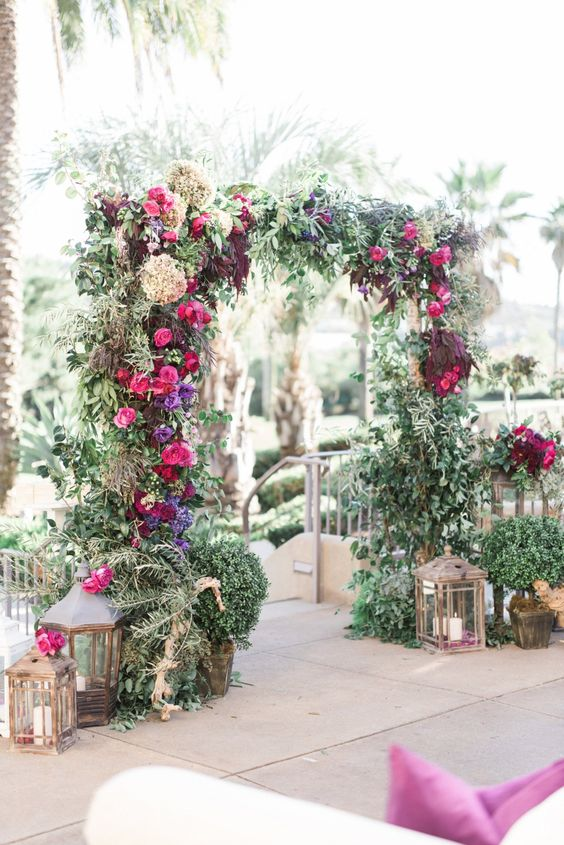 lush greenery wedidng arch with fuchsia, violet and burgundy blooms