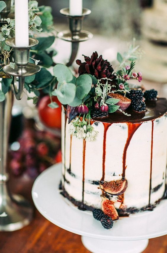 white wedding cake topped with blackberries, figs, blooms and pomegranate dripping