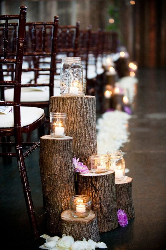 tree stumps with white petals and candle holders
