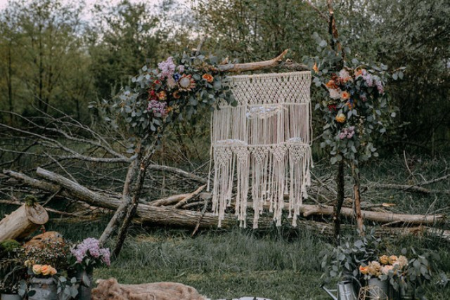 The wedding arch was decorated with greenery, flowers and a macrame backdrop