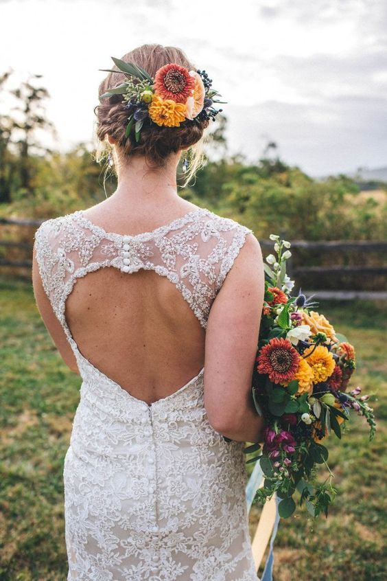 a braided updo with lush bold fall flowers for accentuating