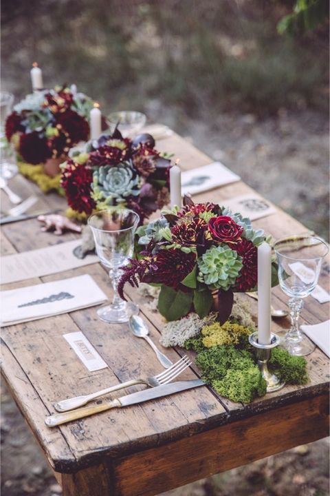 a rustic table with burgundy flowers and succulents and candles for a rustic shower