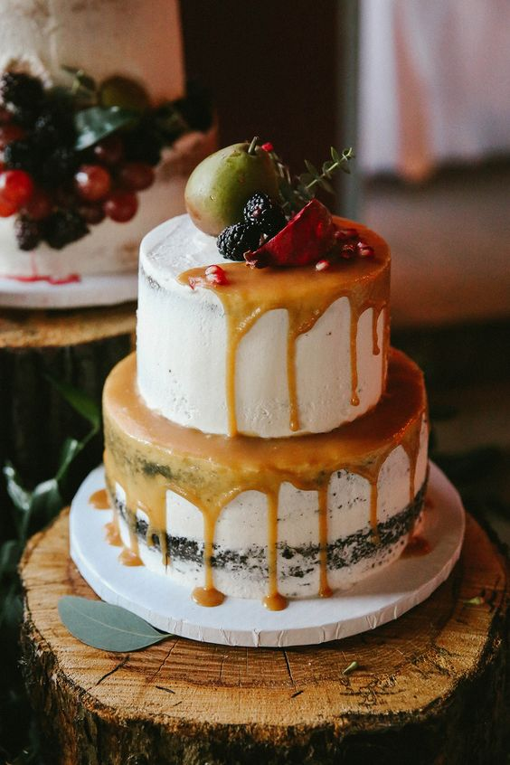 semi naked cake with caramel drip, topped with a pear, blackberries and a pomegranate