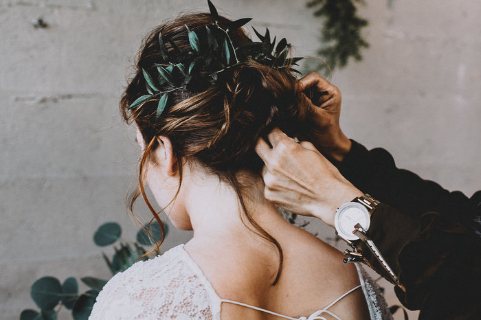 The wedding hairstyle was a messy updo with a green branch