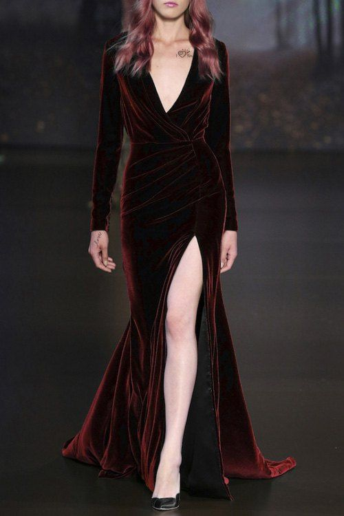 a burgundy velvet bridesmaid's dress with long sleeves, a deep V-neckline and a front slit