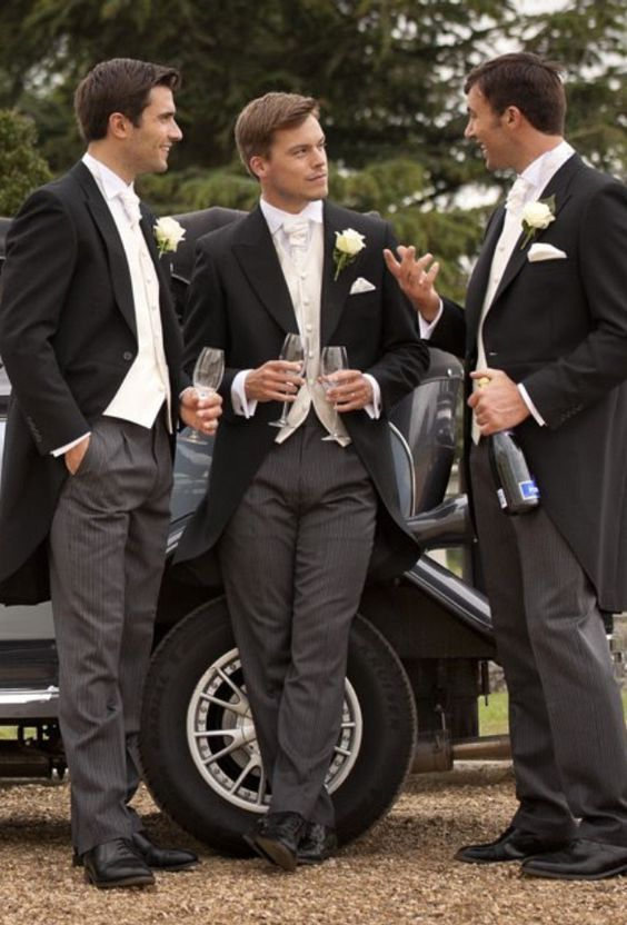 groomsmen in black and grey striped morning suits with white roses for buttonholes