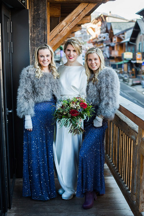 The bridesmaids were wearing navy sparkling dresses and faux fur coverups