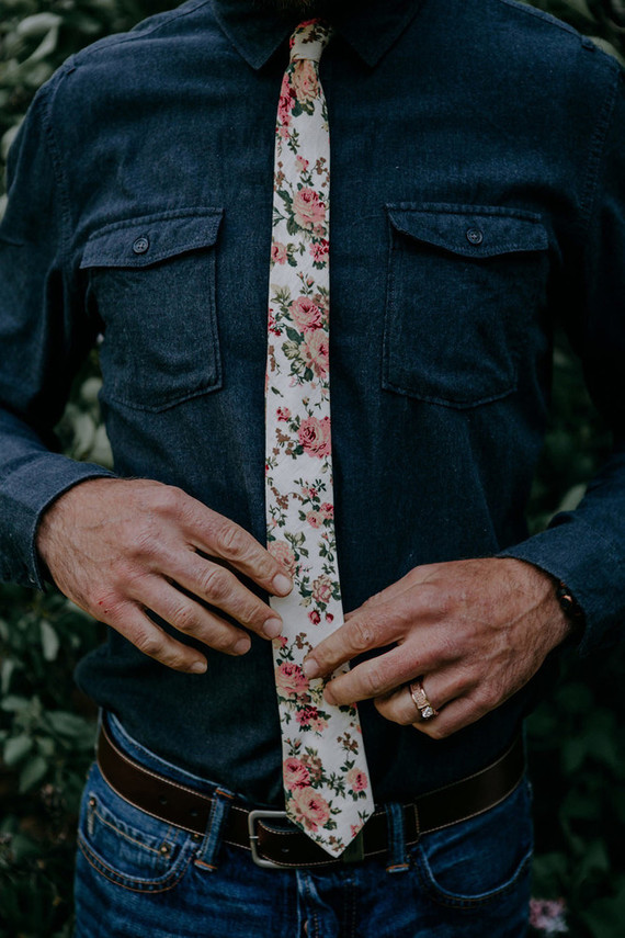 The groom was wearing blue jeans, a chambray shirt and a light-colored floral tie