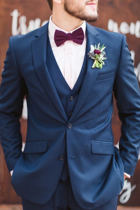 a navy wedding suit with a white shirt, a burgundy bow tie and a burgundy floral boutonniere