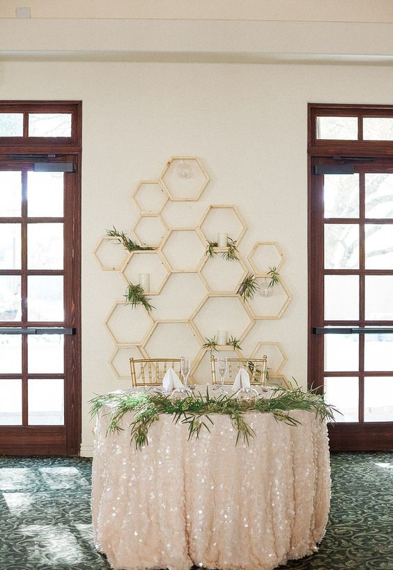gold hexagon sweetheart table backdrop with fresh greenery