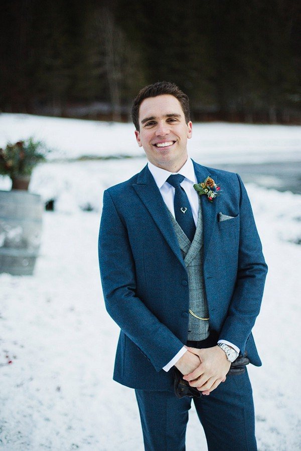 The groom was wearing a blue tweed suit with a grey vest and a tie, it was accessorized in winter style