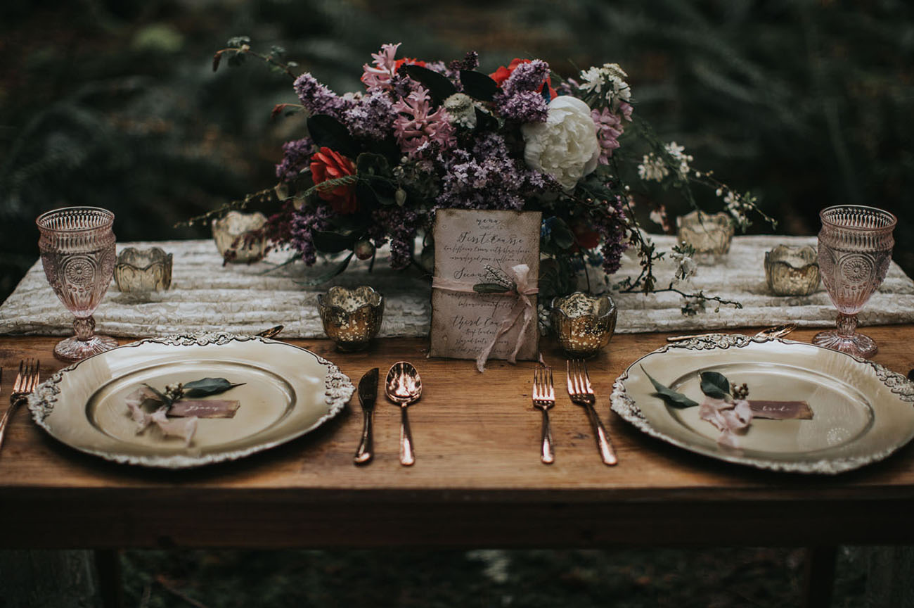 The wedding tablescape was don with silver dishes, copper flatware, pink glasses and mercury glass candle holders, and the florals looked rather wild style
