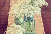 05 a burlap table runner with candles and baby's breath in blue jars is a great way to decorate the tables