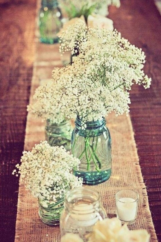 a burlap table runner with candles and baby's breath in blue jars is a great way to decorate the tables