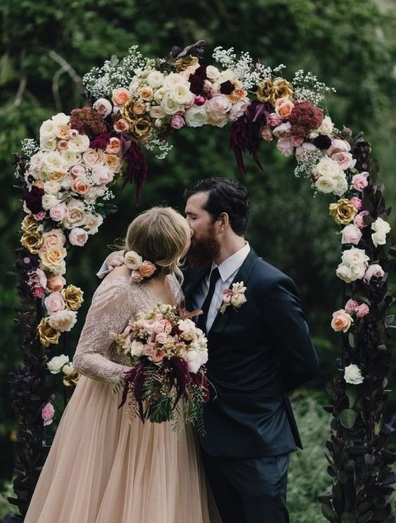a moody floral wedding arch with blush roses and dark purple blooms