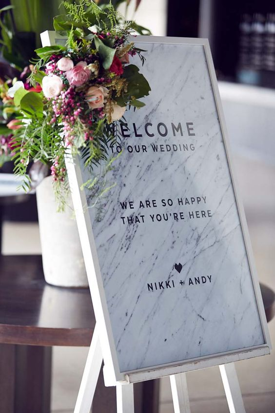 framed marble welcome sign with greenery and flowers on the corner