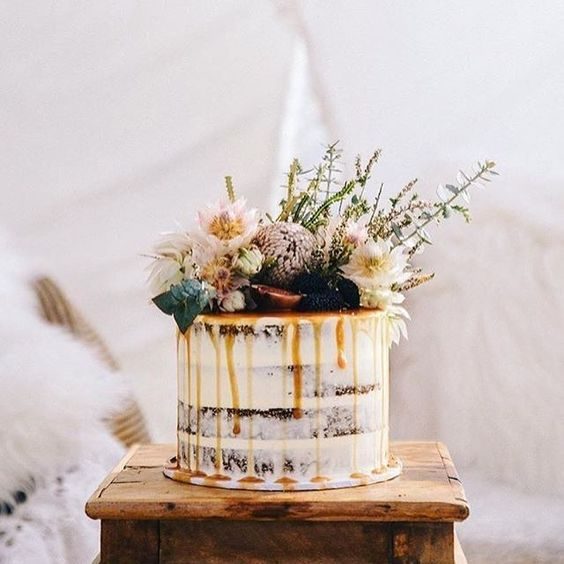 semi naked wedding cake with caramel drip, blackberries, fresh blooms and even grass