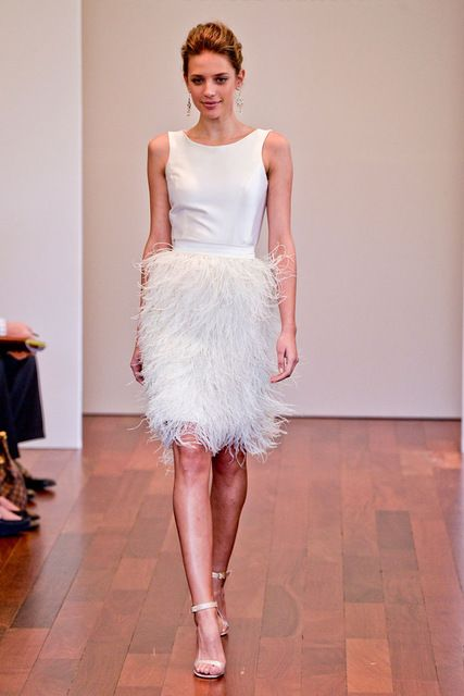 short sleeveless wedding dress with a plain bodice and a feather skirt
