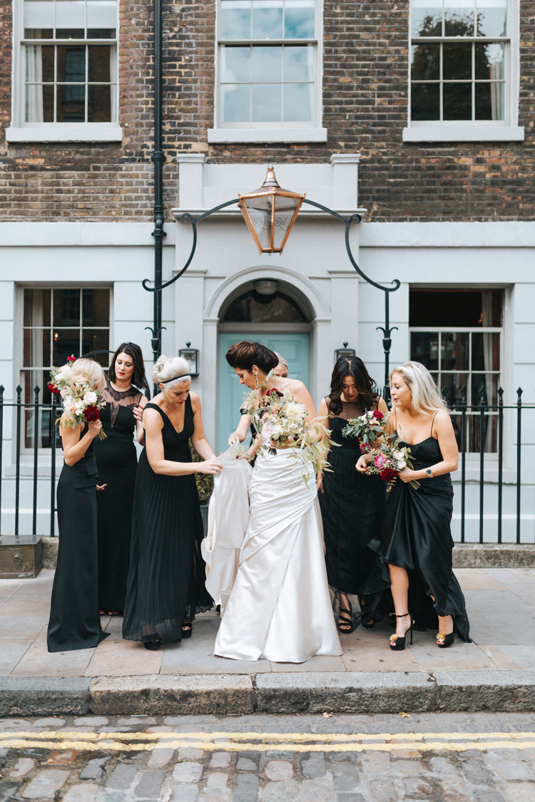 The bridesmaids wore mismatched black long wedding dresses, and 40s earrings from the bride's grandmother collection tied up their looks