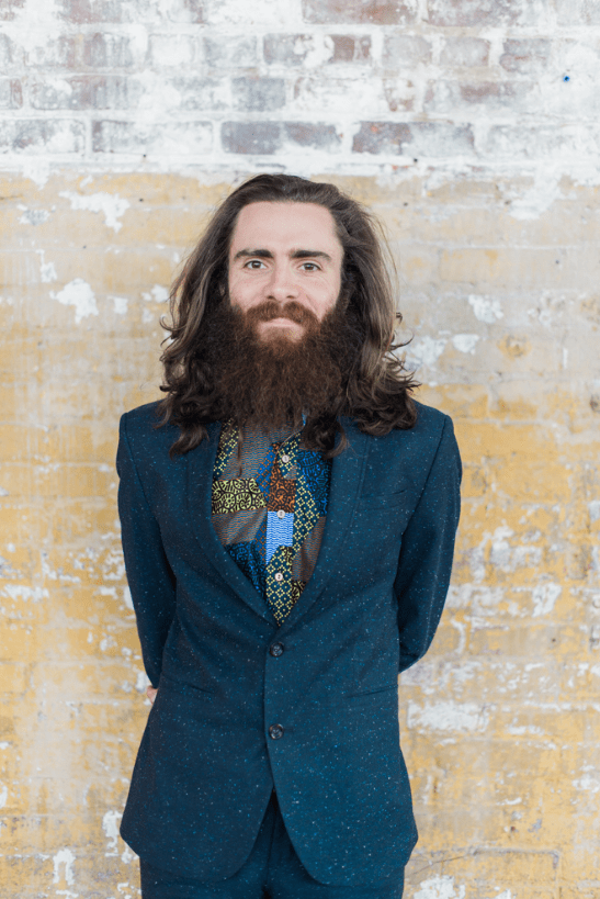 The groom was wearing a printed blue suit with a patchwork shirt and a beard