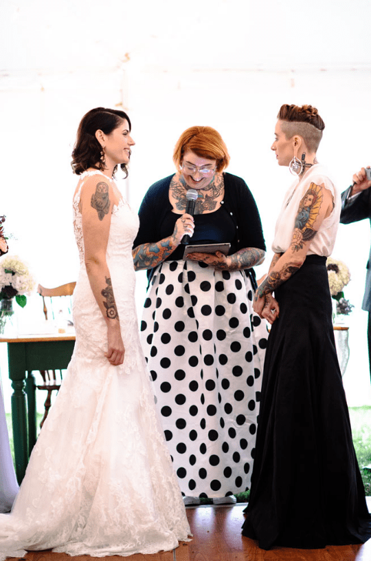 The second bride rocked a black maxi skirt and a white V-neck sleeveless top to show off her tattoos