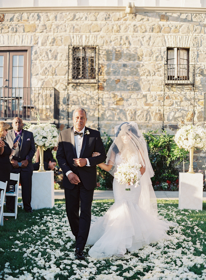 The wedding aisle was covered with white petals and decorated with white florals on stands