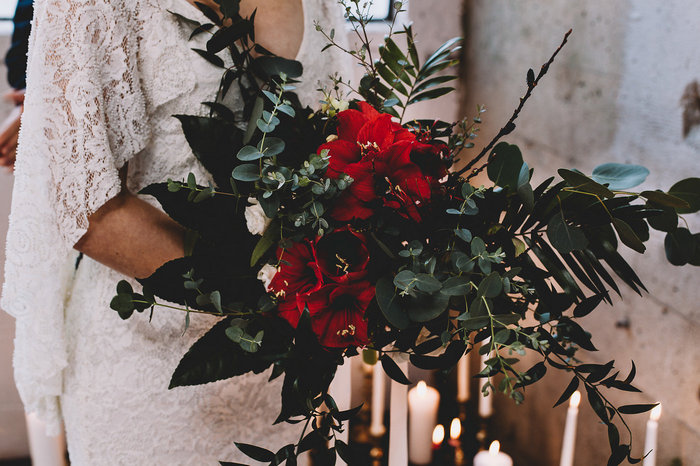The wedding bouquet was a green, white and bold red one, with a lot of greenery