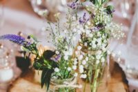 06 a wood slice with mason jars with wildflowers for a rustic centerpiece
