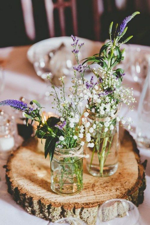 a wood slice with mason jars with wildflowers for a rustic centerpiece
