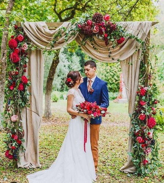 neutral fabric arch with vines and lush red florals