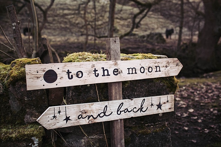 A rustic wedding sign with the moon, sun and stars motifs