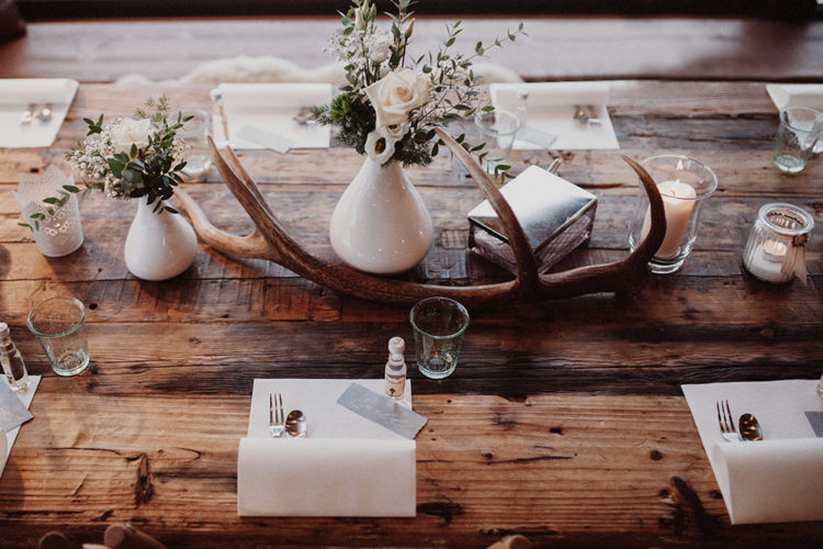 The wedding tablescape was simple and rustic, with antlers, pastel blooms and candles