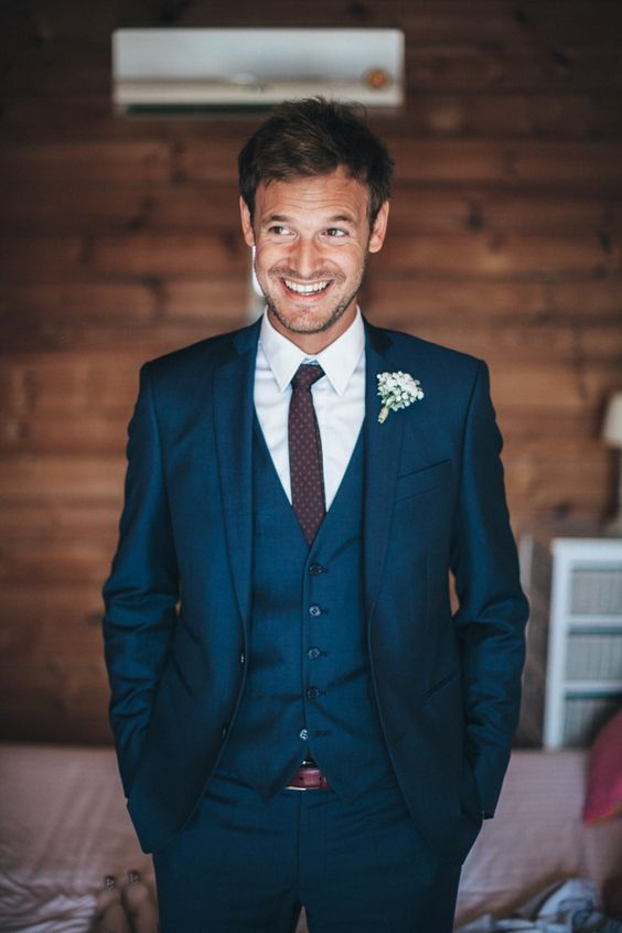 a cool navy three-piece suit with a polka dot burgundy tie is a win-win idea