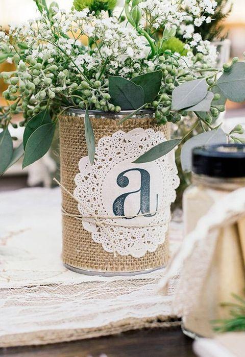 eine Blechdose verpackt, die mit sackleinen und mit einem doily, viel grün und Blumen, die Sie für einen Tafelaufsatz