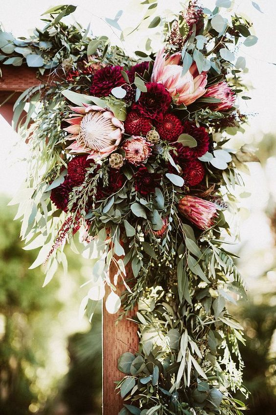 greenery, red dahlias and king proteas for wedding arch decor