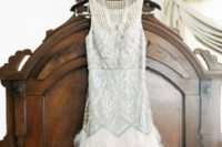 07 short sleeveless wedding dress with silver embroidery and a feather border on the skirt
