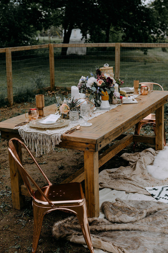 The wedding tablescape was with a macrame table runner, copper mugs, candles and gilded edge plates