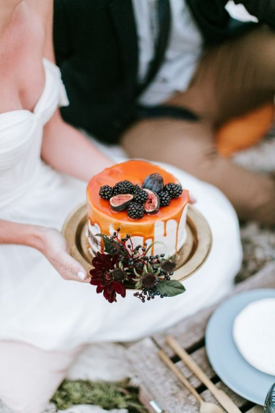 a small wedding cake with salted caramel drip, blackberries and figs