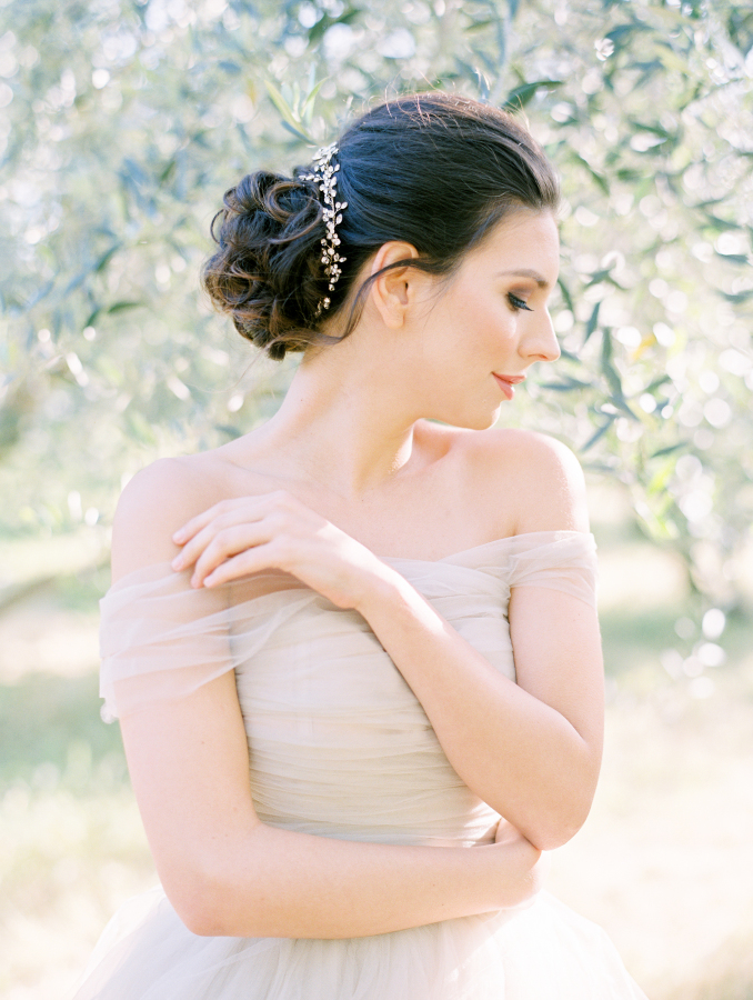 The bride was wearing a curly updo with a beaded hairpiece and a natural makeup look