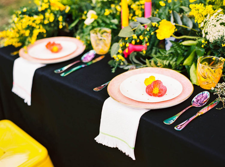 The table setting was done with a black tablecloth, pink plates, colorful flatware and neon-colored candles