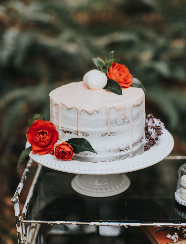The wedding cake was a semi-naked one, with pink glazing, topped with orange blooms and macarons