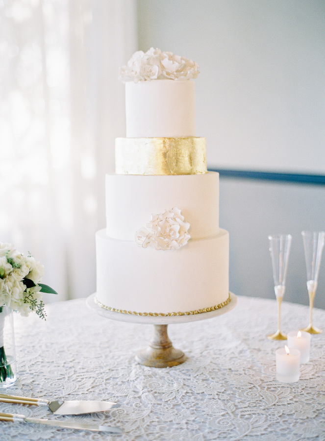 The wedding cake was elegant, in white and with touches of gold, with cream flowers on top