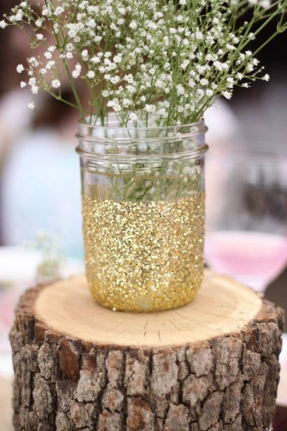 a wooden piece with a glittered mason jar and baby's breath for a centerpiece
