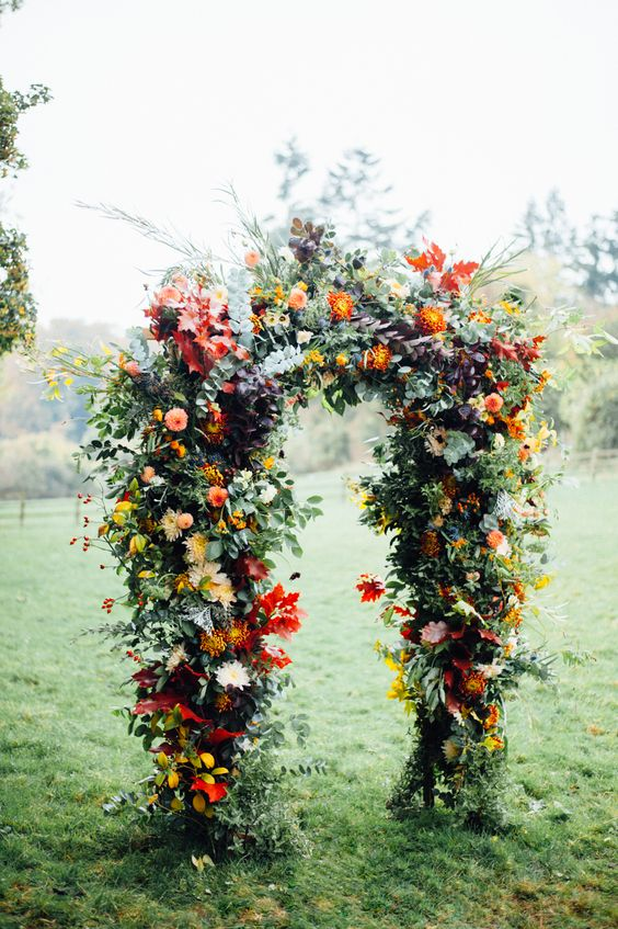 lush wedding arch with orange and blush flowers, greenery and red leaves