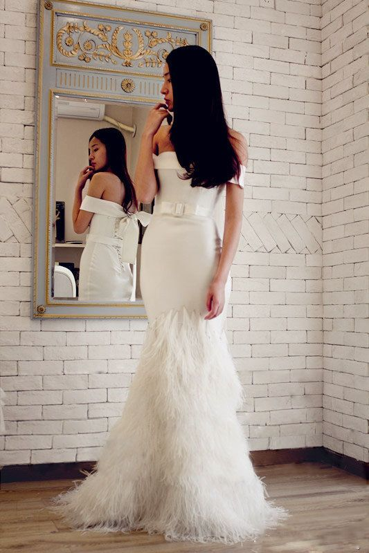 off the shoulder mermaid wedding dress with a belt and a feathered skirt
